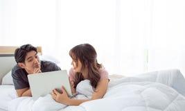 一对逗人喜爱的夫妇在卧室一起使用膝上型计算机 免版税库存图片