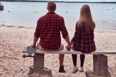 一对逗人喜爱的行家夫妇的后面看法,坐长凳在海滩中间并且观看海 库存图片