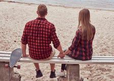 一对逗人喜爱的行家夫妇的后面看法,坐长凳在海滩中间并且观看海 免版税库存照片
