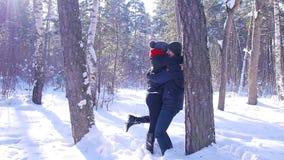 一对年轻和爱恋的夫妇在树附近使用在冬天森林里 影视素材