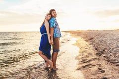 一对年轻夫妇享受中间夏天黄昏,在湿圣 免版税库存图片