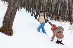 一对年轻夫妇在冬天森林里 免版税图库摄影