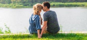 一对年轻夫妇是浪漫的在湖的公园 男人和妇女在绿草的夏天太阳坐 库存图片