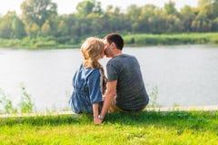 一对年轻夫妇是浪漫的在湖的公园 男人和妇女在绿草的夏天太阳坐 免版税库存图片
