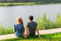 一对年轻夫妇是浪漫的在湖的公园 男人和妇女在绿草的夏天太阳坐 库存照片