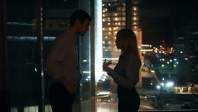 一对年轻夫妇有一个困难的关系 反对俯视夜城市的一个大窗口的背景 股票视频