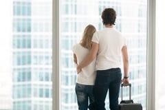 一对年轻夫妇的背面图临近窗口 免版税库存图片
