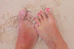 一对年轻夫妇的赤脚在湿沙子的 免版税库存图片