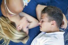 一对年轻夫妇的顶视图在一起说谎在草的爱的 库存图片