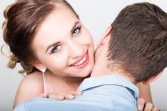 一对年轻夫妇,人的特写镜头在爱的站立与他的回到照相机,女孩微笑 嬉戏的夫妇 免版税库存照片