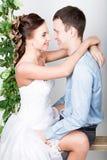 一对年轻夫妇,人的特写镜头在爱的站立与他的回到照相机,她咬住他的耳朵 嬉戏的夫妇 她的腿 免版税图库摄影