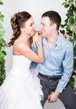一对年轻夫妇,人的特写镜头在爱的站立与他的回到照相机,她咬住他的耳朵 嬉戏的夫妇 她的腿 免版税库存图片