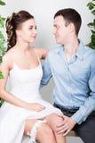 一对年轻夫妇,人的特写镜头在爱的站立与他的回到照相机,她咬住他的耳朵 嬉戏的夫妇 她的腿 免版税库存照片