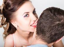 一对年轻夫妇,人的特写镜头在爱的站立与他的回到照相机,她咬住他的耳朵 嬉戏的夫妇 免版税库存图片