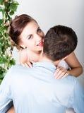 一对年轻夫妇,人的特写镜头在爱的站立与他的回到照相机,她咬住他的耳朵 嬉戏的夫妇 库存图片