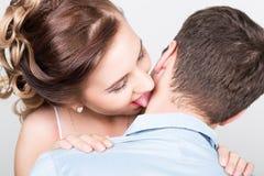 一对年轻夫妇,人的特写镜头在爱的站立与他的回到照相机,她轻轻地接触舌头到他的脖子 免版税库存图片