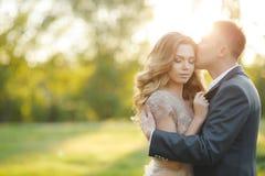 一对年轻婚礼夫妇的浪漫片刻在夏天草甸的 库存图片