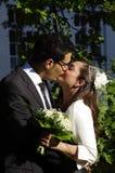 一对年轻西班牙夫妇的婚姻的亲吻 免版税库存图片