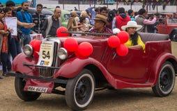 一对年迈的夫妇驾驶他们的奥斯汀葡萄酒汽车,在旗子在政治家葡萄酒汽车集会后 免版税库存照片