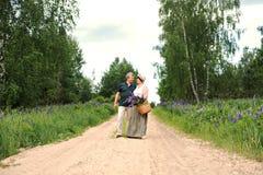 一对年长夫妇通过森林走,并且一个人给妇女与紫色羽扇豆花花束的一个被编织的篮子  免版税图库摄影