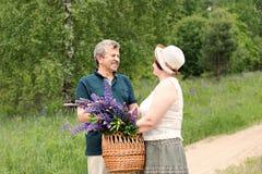 一对年长夫妇通过森林走,并且一个人给妇女与紫色羽扇豆花花束的一个被编织的篮子  免版税库存照片