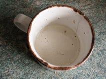 一小白色和黑被察觉的杯有一个生锈的外缘的和有A的 免版税库存图片