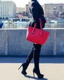 一少妇时尚博客作者沿江边走一套黑时髦衣服的,高跟鞋和有一个大红色提包的 图库摄影