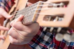一少妇` s的特写镜头递弹吉他 免版税库存图片