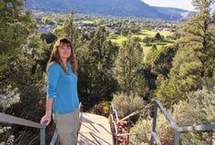 一层楼梯的一名可爱的妇女在高尔夫球场上 库存照片