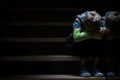一层楼梯的男孩在晚上 库存照片