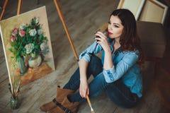 绘一幅画的妇女艺术家在演播室 免版税库存照片