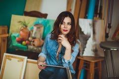 绘一幅画的妇女艺术家在演播室 免版税库存图片