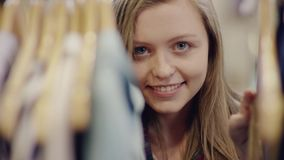 一年轻俏丽妇女寻找的接近的射击在一个机架的衣裳在服装店 股票录像