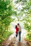 一年轻加上走沿秋天公园的狗她是在他是在与一条多壳的萨莫耶特人狗的白色的一件红色毛线衣 库存照片