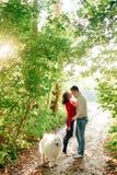 一年轻加上走沿秋天公园的狗她是在他是在与一条多壳的萨莫耶特人狗的白色的一件红色毛线衣 库存图片