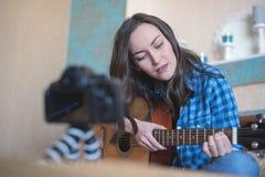一年轻博客作者在DSLR照相机训练录象在声学吉他写使用 免版税库存照片