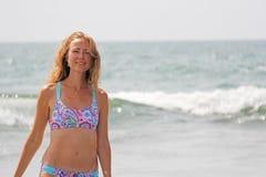 一年轻和美女,佩带的太阳镜,在美丽的分开的泳装和金发、立场和微笑反对 免版税图库摄影