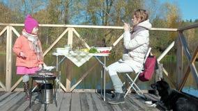 一年轻女人和一女孩衣服暖和、母亲和女儿的,一顿野餐由河一个木桥的,用途 影视素材