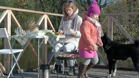 一年轻女人和一女孩衣服暖和的,烹调菜和肉在格栅,附近使用的狗,a 影视素材