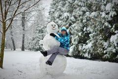 一年轻女人在森林在冬天拥抱一个大雪人 免版税库存图片