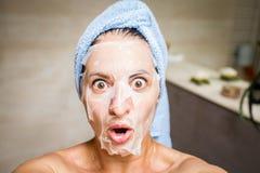 一年轻女人的乐趣selfie有白色面具在她的面孔和浅兰的毛巾的在她的头 免版税图库摄影
