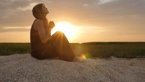 一年轻女人的剪影沙子的在日落,祈祷对天际的神,假期的概念,宗教,bea的女孩 股票视频
