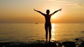 一年轻女人的剪影海滩的在日落期间,在泳装站立并且举她的胳膊对边和 股票视频