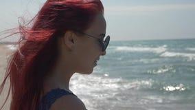 一年轻女人的外形画象有飞行在太阳镜的风的红色头发的和有在她的牙的括号的反对 股票录像
