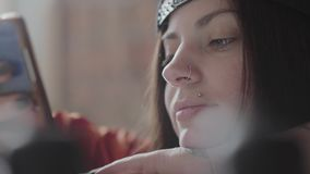 一年轻女人的接近的面孔有被刺穿的嘴唇和圆环的在发短信在手机的鼻子 美丽的异常的女孩 股票录像