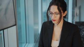 一年轻女人的特写镜头画象一套西装的在工作场所 研究计算机的女商人坐由 股票录像