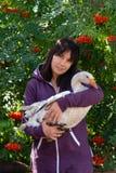 一年轻女人的画象有一只用羽毛装饰的朋友白色鹅的反对花揪用橙色莓果 免版税库存图片