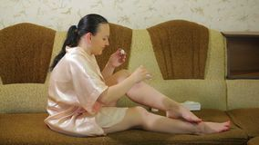 一年轻女人长沙发的在去壳以后在家应用在她的腿皮肤的扑粉  股票视频
