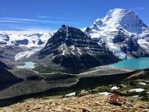 一年轻女性徒步旅行者思考赤裸俯视与一个巨大的山、冰川和绿松石湖的一个难以置信的谷 库存图片
