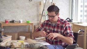 一年轻废人的画象一个轮椅的有参与家具装配电钻的  股票视频
